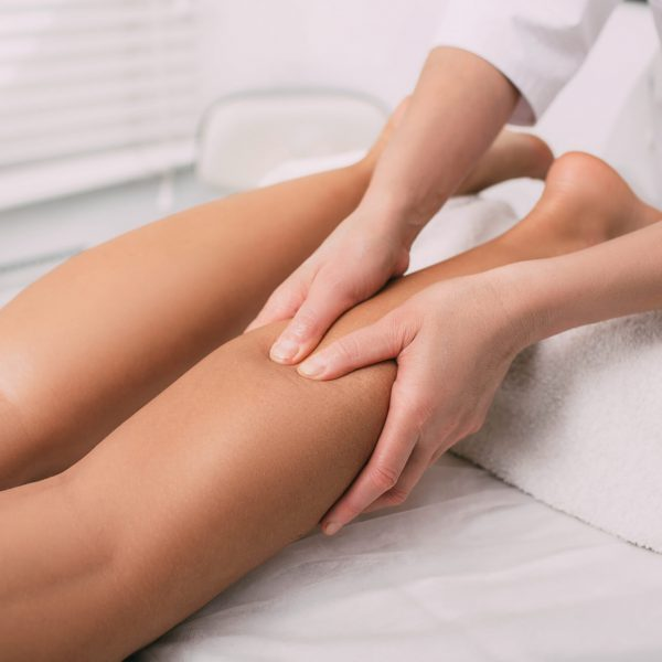 massage therapist makes relaxing leg massage, close-up